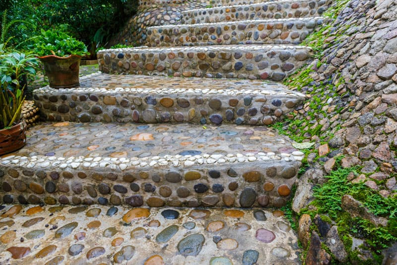 Outdoor steps made of inlaid river stones of various colors.