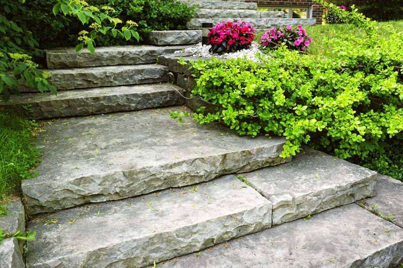 A house's front steps, made of massive, thick slabs of stone.