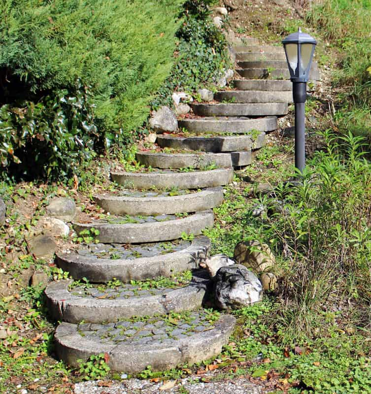A stone staircase and lamp post on a hillside.