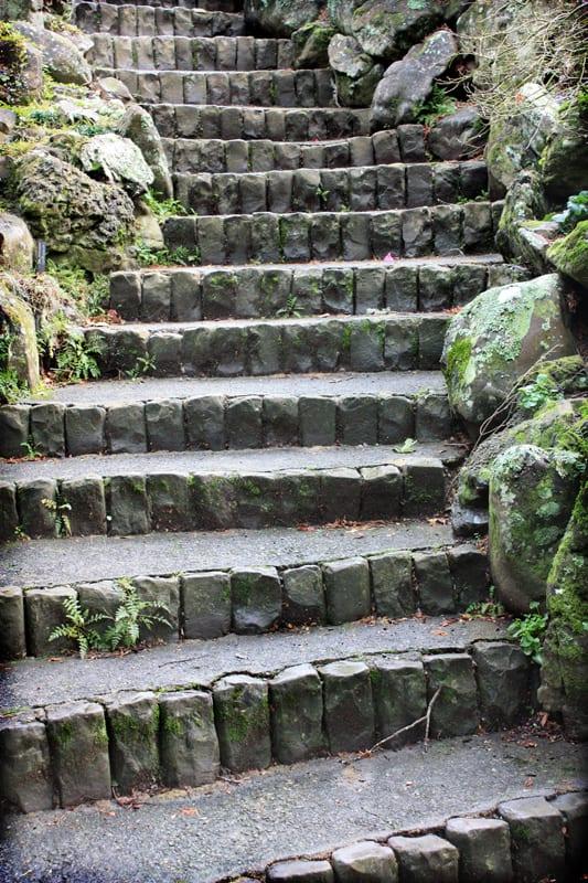 An asian style rock stair case winding up a rocky hillside.
